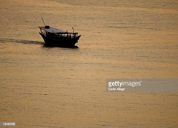 A dhow a type of boats used in the Persian Gulf region crosses the harbor at sunset April 23 2003 in Doha Qatar The distinctive craft is used...