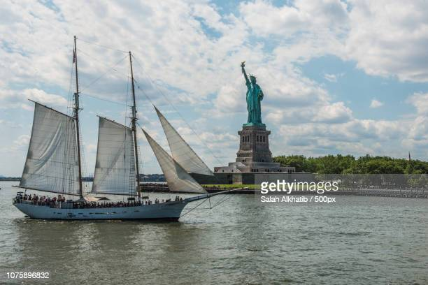 dhow meets statue of liberty - salah stock photos and pictures