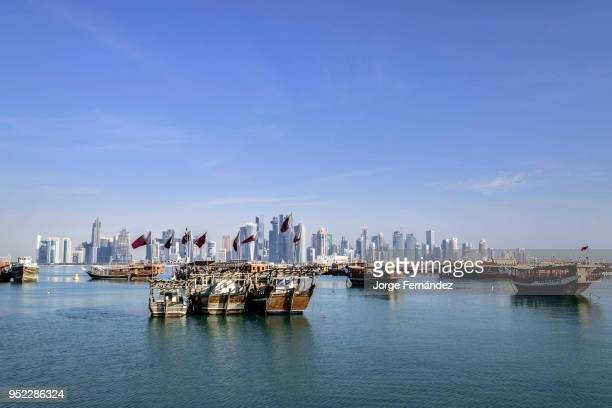 Dhows with Qatar flags anchored in Doha West Bay