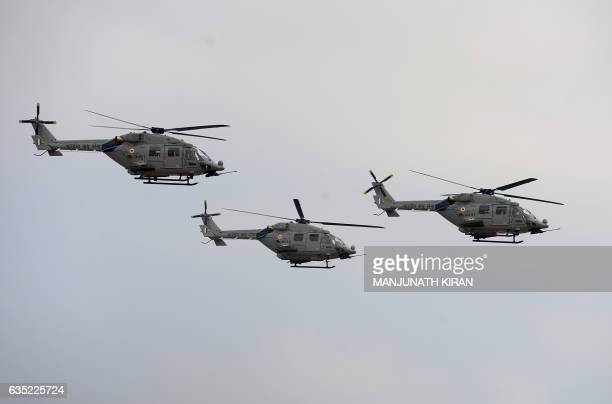 Dhruv helicopters of the Indian Air Force perform a fly past on the inaugural day of the 11th edition of 'Aero India' a biennial air show and...