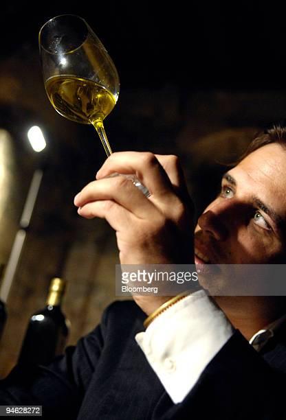 Di Bennardo maker of Di Bennardo L'Olio d'Oliva owner Giovanni Di Bennardo checks the color of olive oil at an olive oil tasting in a medieval wine...