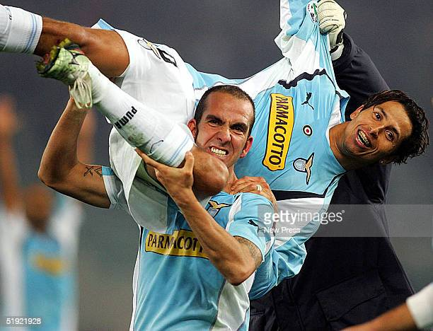 Di Canio of Lazio carries teammate Cesar after their victory over Roma during the Serie A match between Lazio and Roma at the Olympic Stadium January...