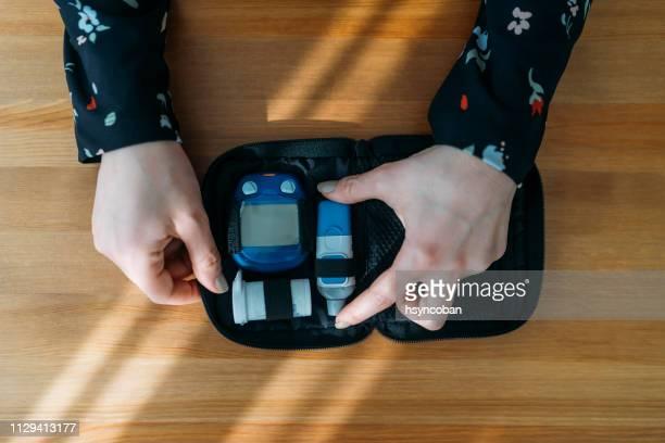 diabetes doing blood glucose measurement - lancet arch stock pictures, royalty-free photos & images