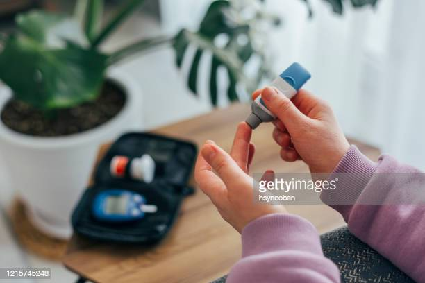 diabetes doing blood glucose measurement - metabolic syndrome stock pictures, royalty-free photos & images