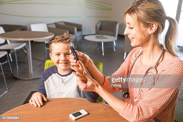 Diabetes health care specialist with a young diabetic patient