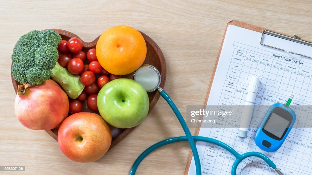 Diabetes monitor, Cholesterol diet and healthy food eating nutritional concept with clean fruits in nutritionist's heart dish and patient's  blood sugar control record with diabetic measuring tool kit : Stock Photo