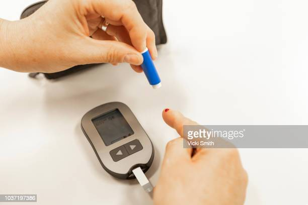 diabetic finger prick test - glucose stock pictures, royalty-free photos & images