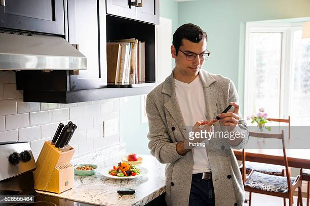 Diabetic Latino man monitoring his blood sugar levels