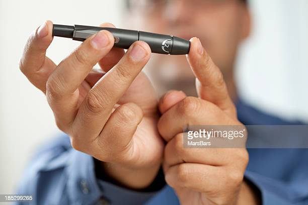 Diabetic man pricking finger for glucose test