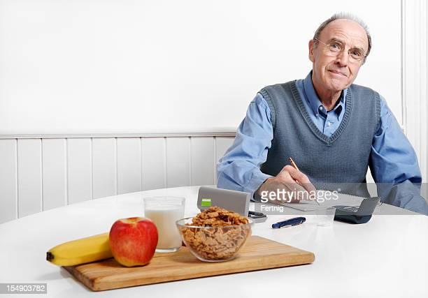 Diabetische Mann Aufnahme seiner blood sugar-Etage oder Angabe über deinen Kalorienverbrauch