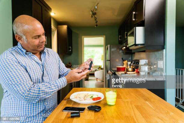 A diabetic mixed race man in his fifties testing his blood sugar