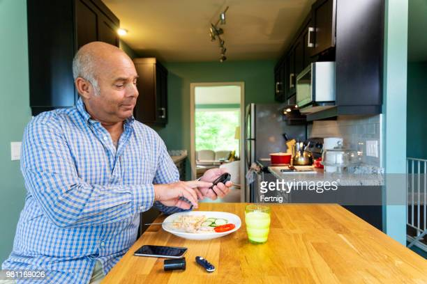 a diabetic mixed race man in his fifties testing his blood sugar - fat nutrient stock pictures, royalty-free photos & images