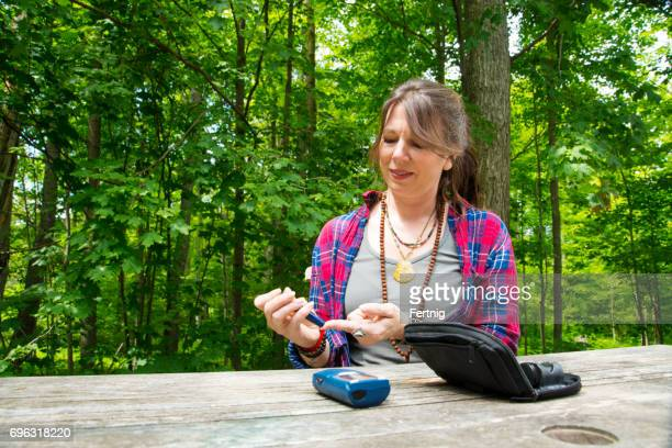 Diabetic patient checking her blood sugar at home