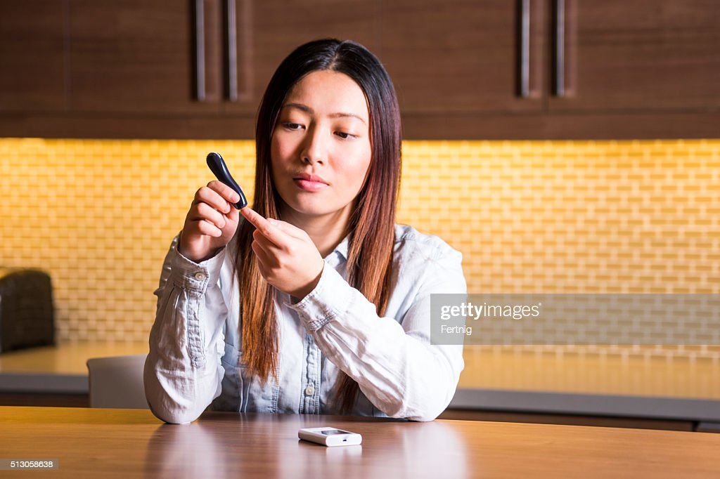 Diabetic patient checking her blood sugar levels : Stock Photo