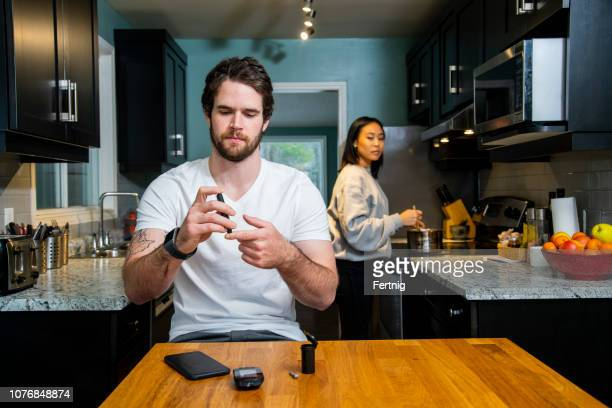 a diabetic patient checking his blood sugar using a glaucometer and a smart device. - diabetes stock pictures, royalty-free photos & images
