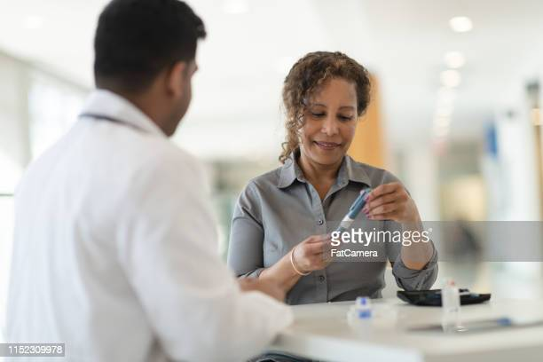 diabetic patient meets with her doctor - hormone stock pictures, royalty-free photos & images