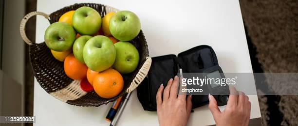 diabetic person performing a glucose level blood test at home - glycemia stock pictures, royalty-free photos & images