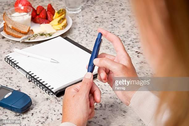 diabetische frau, die ihr blut sugar etagen - food journal stock-fotos und bilder