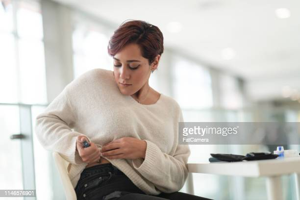 diabetic woman uses insulin pen - diabetes stock pictures, royalty-free photos & images