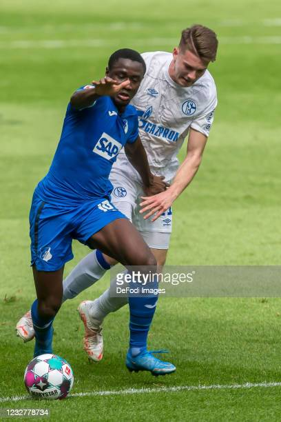 Diadie Samassekou of TSG 1899 Hoffenheim and Florian Flick of FC Schalke 04 battle for the ball during the Bundesliga match between TSG Hoffenheim...