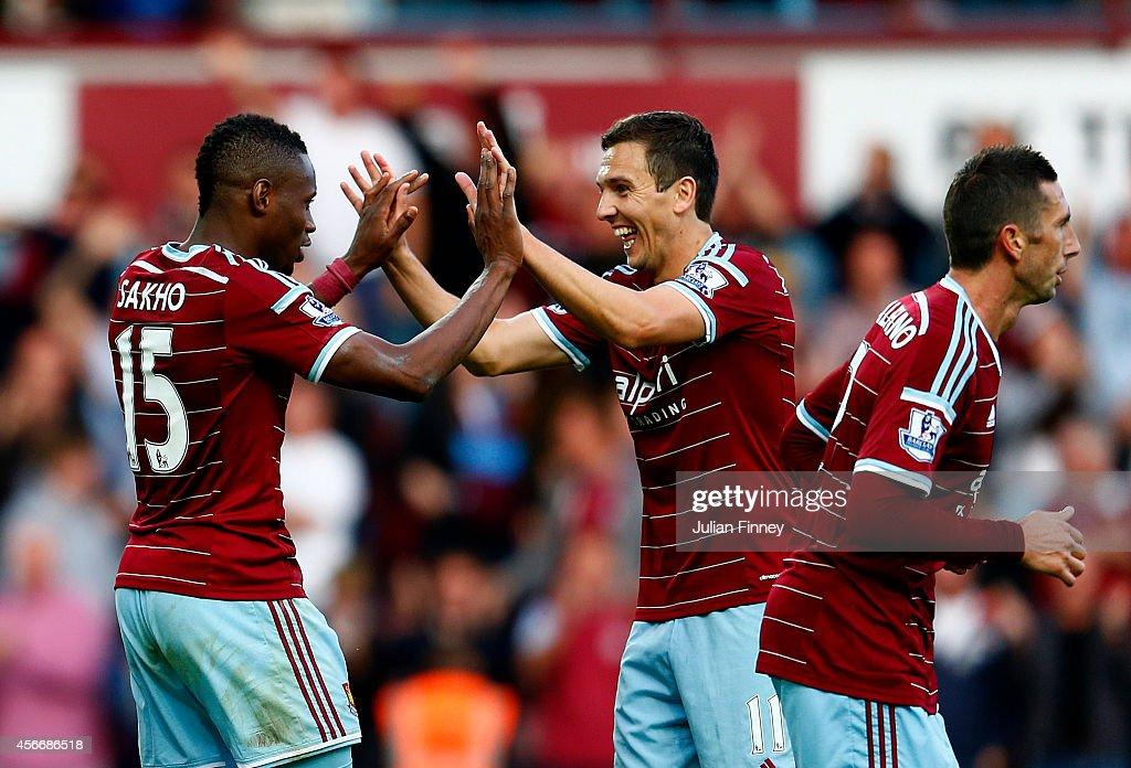 Diafra Sakho of West Ham celebrate with team-mate Stewart Downing after scoring his team's second goal during the Barclays Premier League match between West Ham United and Queens Park Rangers at Boleyn Ground on October 5, 2014 in London, England.