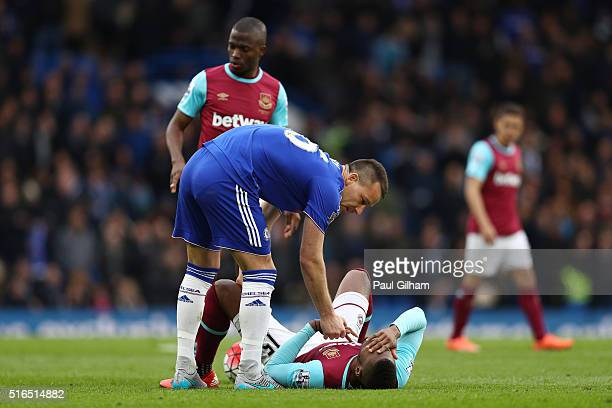 Diafra Sakho of West Ham United lies injured while John Terry of Chelsea talks to him during the Barclays Premier League match between Chelsea and...