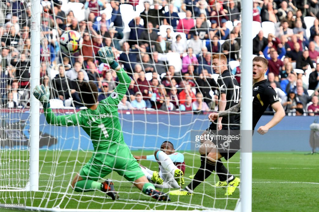 Diafra Sakho of West Ham United scores the opening goal past Lukasz Fabianski of Swansea City during the Premier League match between West Ham United and Swansea City at London Stadium on September 30, 2017 in London, England.