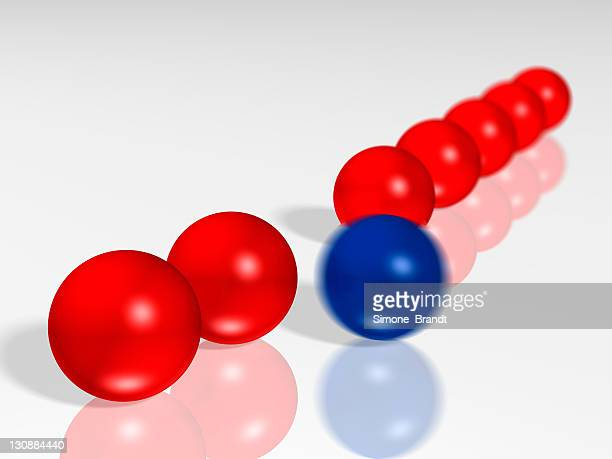 Diagonal row of shiny red glass balls, one blue ball standing apart, blurred from motion, 3-D cutout