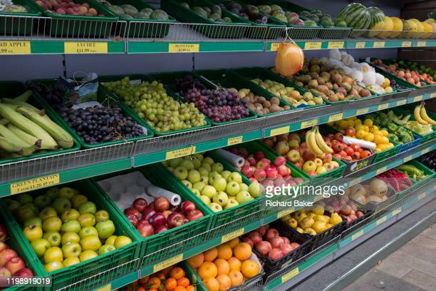 Diagonal view of an exterior of a local corner shop stocking loose nutritious fruit and veg from the shelves including oranges, bananas, apples and...