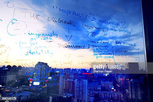 Diagram and words on glass window with cityscape