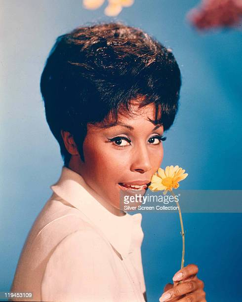 Diahann Carroll US actress and singer poses with a yellow flower in a studio portrait against a blue background issued as publicity for the US...