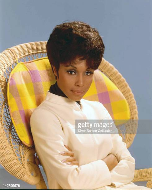 Diahann Carroll US actress and singer wearing a white jacket and sitting in a wicker chair with a pink and yellow check cushion in a studio portrait...