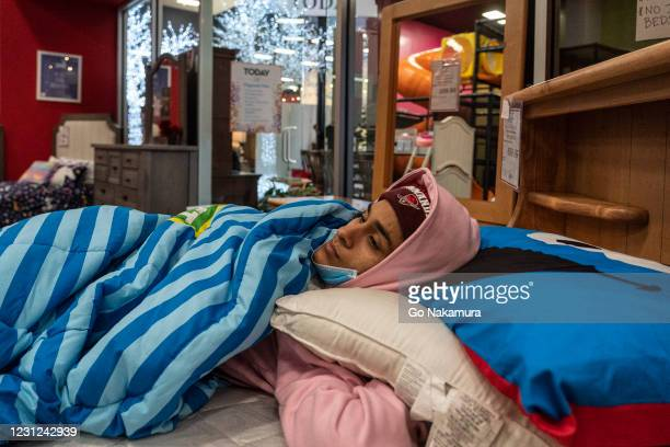 Dialina Ganzo rests on a bed while taking shelter at Gallery Furniture store which opened its door and transformed into a warming station after...