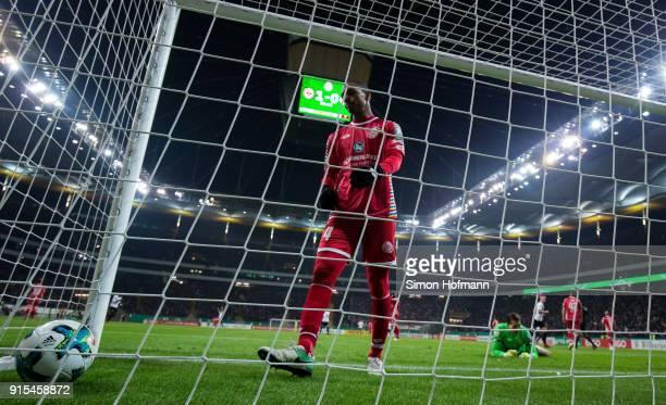 Diallo Abdou of Mainz looks dejected as he picks up the ball after an own net goal during the DFB Cup quarter final match between Eintracht Frankfurt...