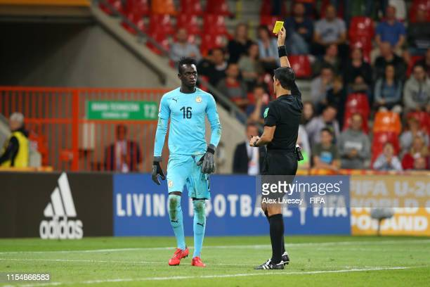 Dialy Ndiaye of Senegal is shown a yellow card by referee Leodan Frankin Gonzalez Cabrera for moving off his line too soon in the penalty shoot out...