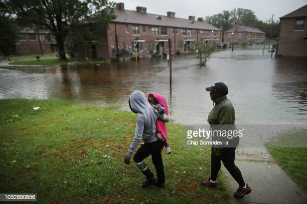 Diamond Dillahunt 2yearold TaLayah Koonce and Shkoel Collins survey the flooding at the Trent Court public housing apartments after the Neuse River...