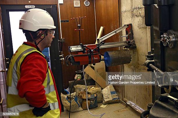Diamond driller Sunny Kirby looks on as a drill is positioned to drill another hole in the wall used by burglars to access the underground vault of...