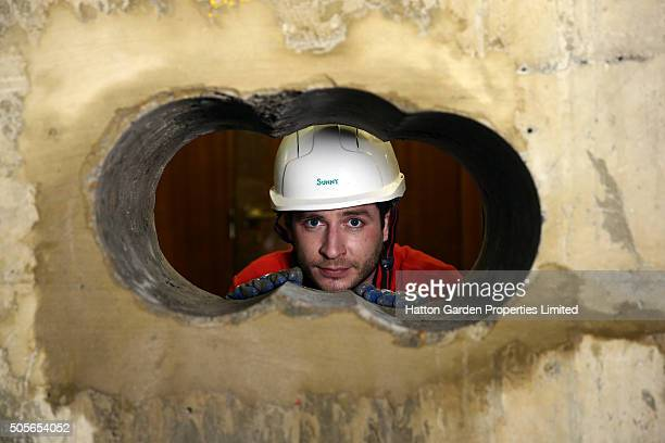 Diamond driller Sunny Kirby looks through the hole used by burglars to access the underground vault of the Hatton Garden Safe Deposit Company which...