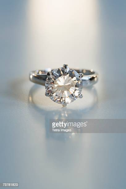 Diamond like ring in six pronged silver setting on table