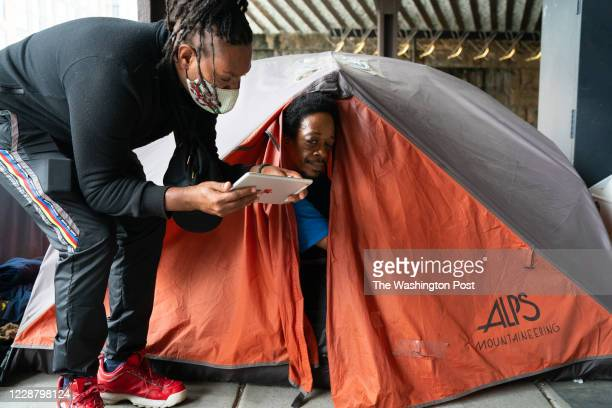 Diamond Miles, left, an outreach workers with h3 helps Montrell Williams fill out the U.S. Census on September 26, 2020 in Washington, DC. Ami...