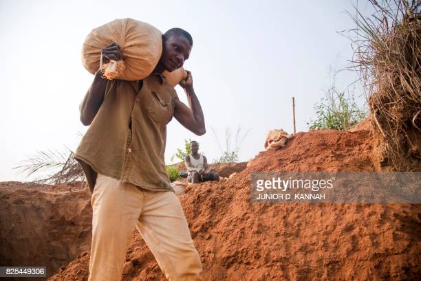 Diamond miner Banayi Ilunga carries gravel as he works with his friends at the Nkanzala abandoned mine in order to find something to support his...