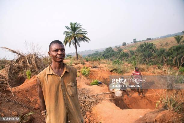 Diamond miner Banayi Ilunga poses for a photograph as he works with his friends at the Nkanzala abandoned mine in order to find something to support...