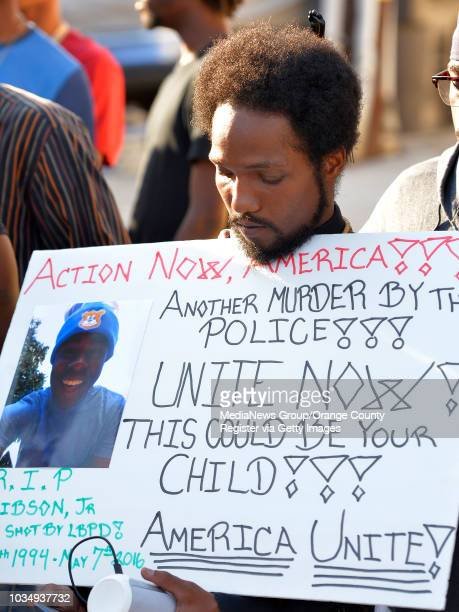 Diamond Mundy holds a sign as he attends a vigil for Lionel Gibson in Long Beach CA on Wednesday May 18 2016 A couple dozen family friends and people...