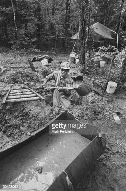Diamond prospector Jim Archer digging deep hole in the mud w. Bucket shovel as he fills nearby trough w. Slop to be screened for diamonds at Crater...