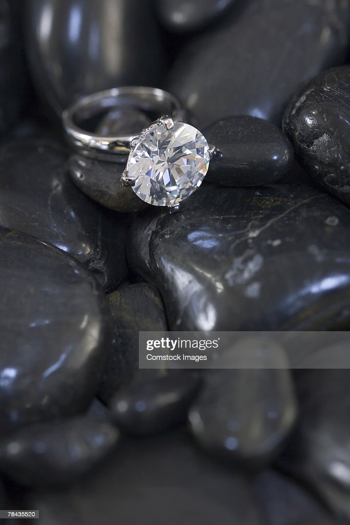 Diamond ring resting on stones : Stockfoto