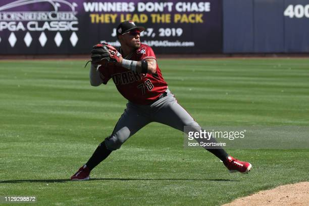Diamondback Juniel Querecuto fires to first too late to get Brewers Lorenzo Cain during a spring training game between the Arizona Diamondbacks and...