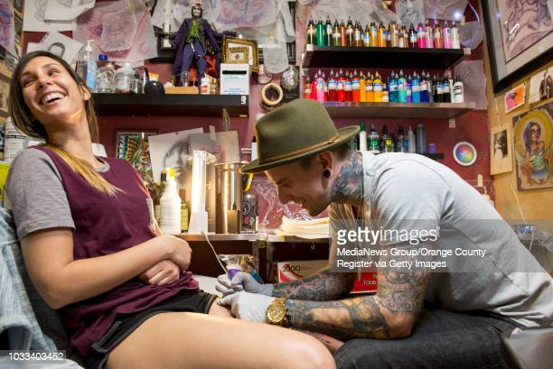 Diana Archer left, of Rialto has artist London Reese of Vatican Studios in Lake Forest do a leg tattoo of the Goddess of Archery on her leg....