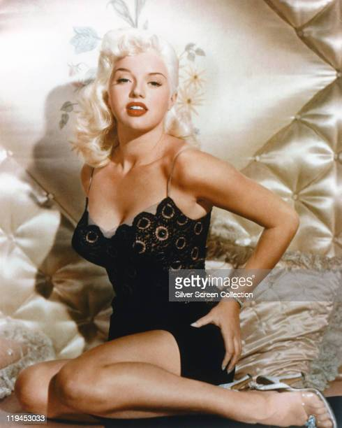 Diana Dors British actress the British 'blonde bombshell' posing on bed with silk bedding circa 1955