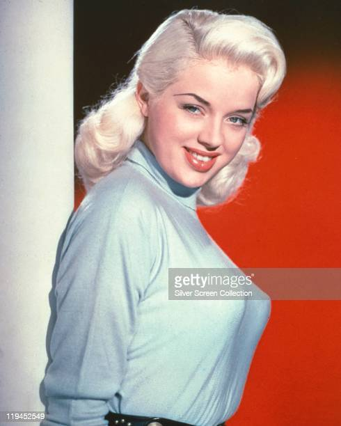 Diana Dors . British actress, wearing a light blue polo neck jumper in a studio portrait, against a red background, circa 1955.