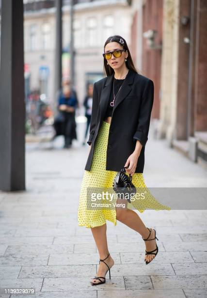 Diana Enciu is seen wearing Dior sunglasses hair clip black bag heels yellow skirt with slit black blazer outside Nanushka brunch during the Budapest...